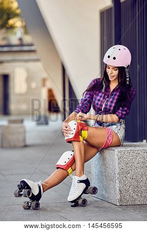 Beautiful girl puts on protective gear for rollerblading. Stylish pink skating helmet, knee pads and quad roller skate.