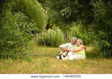 beautiful old people are sitting on the grass in the park