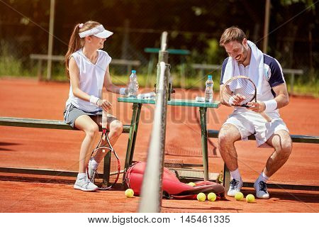 Young man and woman chatting on pause in tennis court
