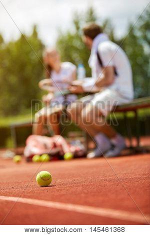 Yellow tennis ball on dross tennis court