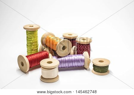 Some wooden spools with satin ribbons on white