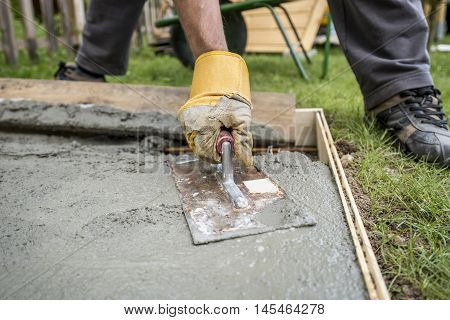 Close up on worker paving or smoothing fresh concrete in plywood walls to be used for an outdoor patio driveway or sidewalk.