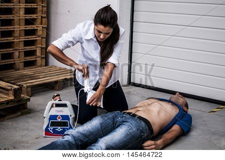girl assisting an unconscious man with defibrillator after heart attack
