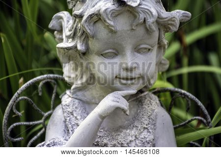 garden statue of young girl angel figurine in outdoor greenery