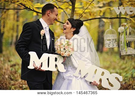 Happy Wedding Couple In Autumn Day With Sign Mrs & Mr