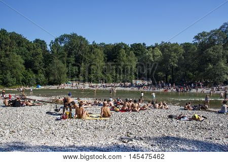 MUNICH, GERMANY - JUNE 4, 2015: The Isar river in Munich with many unidentified people on a sunny day taking a sunbath