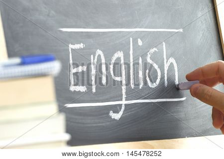 """Hand writing on a blackboard in a language class with the word """"English"""" written on it. Some books and school materials"""