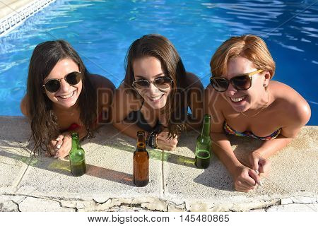 group of three happy and beautiful young girl friends having bath in swimming pool together having fun enjoying drinking beer bottle at summer vacation resort smiling in women holiday concept