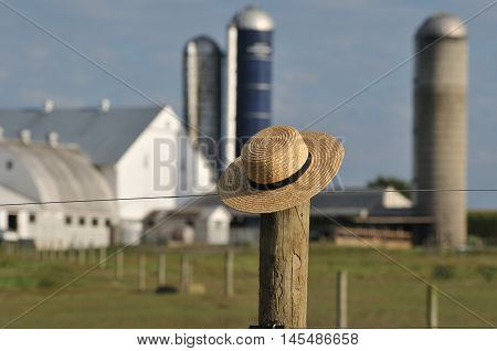 Amish straw hat laying over fence post with Amish farm behind in the background