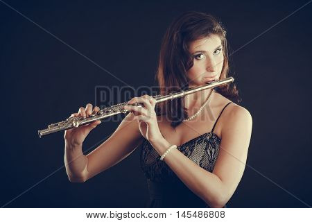 Music and elegance. Alluring elegant woman playing on transverse flute. Female musician with her instrument performing.