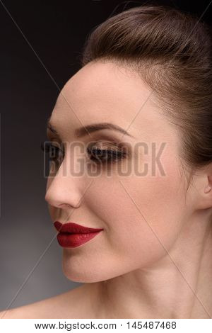 Sly young girl is looking aside and flirting. She has bright make-up and perfect skin. Isolated