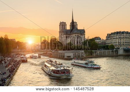Notre Dame de Paris cathedral with cruise ship in Seine river in Paris France. Beautiful sunset in Paris France
