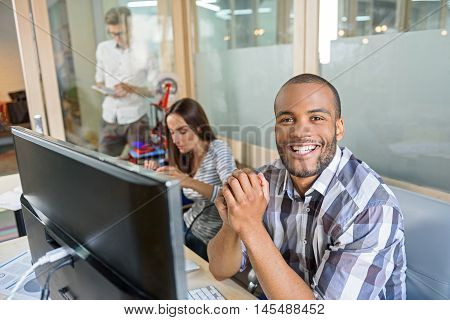 3d printing process. Happy young man is sitting near computer and smiling. His colleagues are working on background