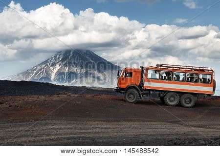 KAMCHATKA RUSSIA - JUNE 24 2016: Russian expedition truck KamAZ (6-wheel drive) on mountain road on background of lava fields and beautiful volcano. Eurasia Russian Federation Far East Kamchatka Peninsula Klyuchevskaya Group of Volcanoes.