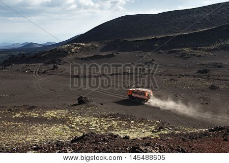 KAMCHATKA PENINSULA RUSSIA - JUNE 24 2016: Russian expedition truck KamAZ (6-wheel drive) transportation tourists on mountain road in the vicinity of the volcano. Eurasia Far East Russia Kamchatsky Region Klyuchevskaya Group of Volcanoes.