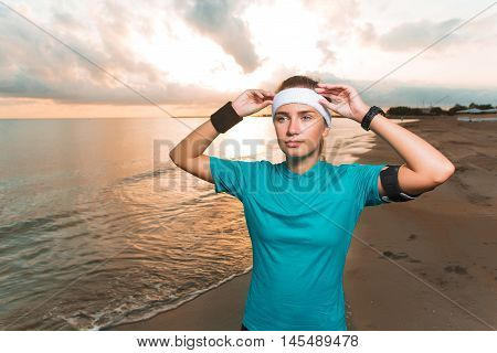 Young Sporty Girl Doing Morning Exercises On Beach At Sunrise