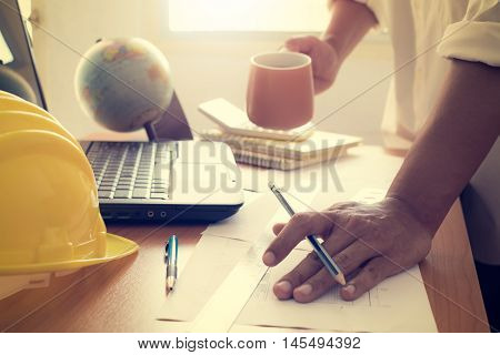 Hands Of Architect Holding Coffee Cup And Working With Construction Plan
