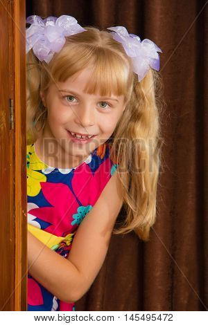Laughing little girl hid behind an old wardrobe . retro style