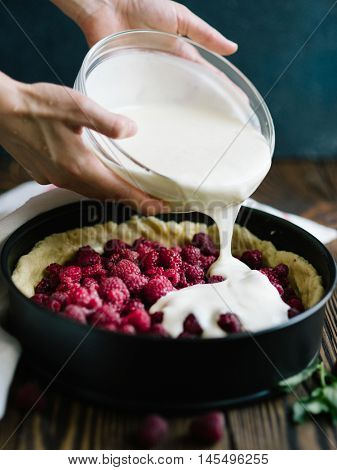 Berry pie making. A pie with raspberry on a wooden background, top view