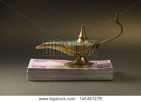 'Get rich' - creative concept. An aladdin lamp placed over pile of hundred UAE dirham currency notes.