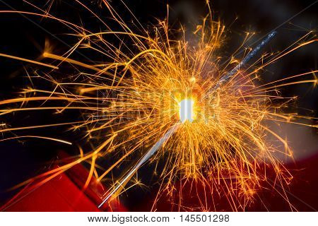 Close up image of a sparkler burned halfway down with sparks flying all around.