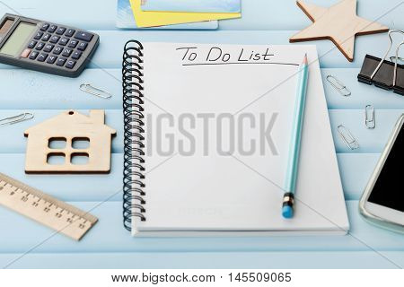 Notebook with to do list and different office tools on blue rustic desk. Planning and design concept.