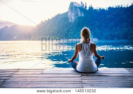 Young woman meditating by the lake, back view, toned image