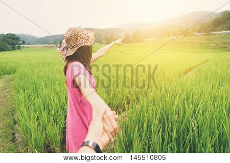Young woman holding man hand and leading on the rice greenfield Vintage tone