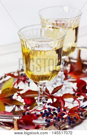 Two glasses of white wine on a vintage silver tray decorated with autumn grape leaves and raspberries, romantic picnic. Focus on the front of the glass.