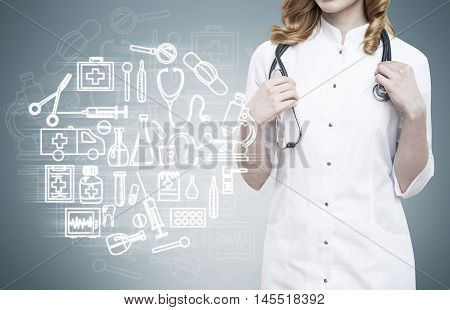 Girl in doctor's gown standing near medicine sketches on gray blackboard. Concept of veterinar work.