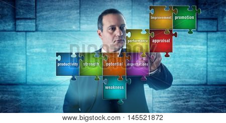 HR manager with focused look touching a jigsaw puzzle imprinted with performance appraisal terms. Concept for career development self assessment human resources management and talent acquisition. poster
