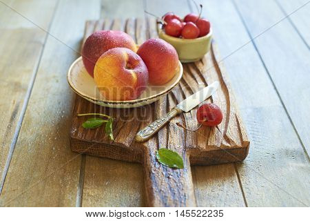 Fresh peaches and sweet cherry on wooden board