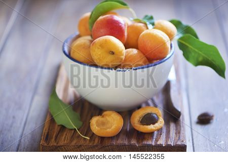 Fresh apricots in white bowl on wooden table
