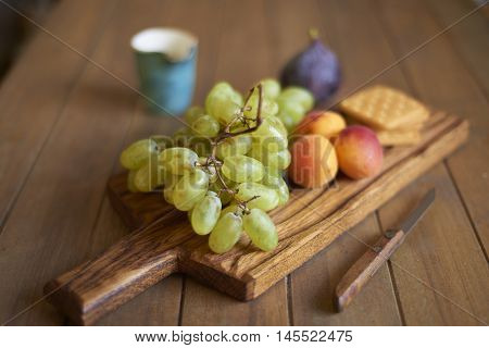 Fresh grapes, apricots and figs with crackers on wooden board