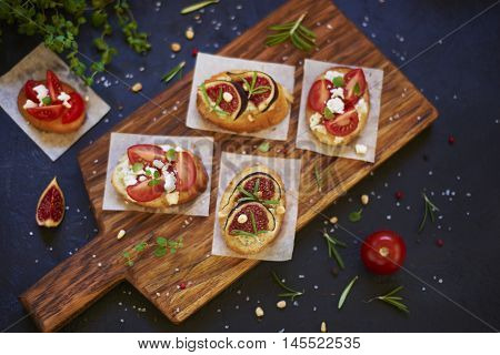 Homemade bruschetta with fig, tomato, cheese, nuts and herbs