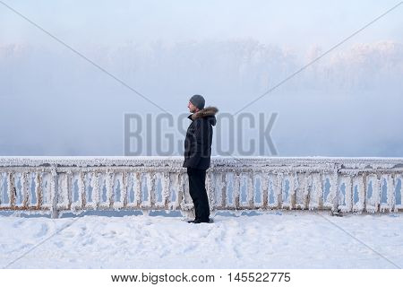 Man standing in front of the fence on a river bank in winter.
