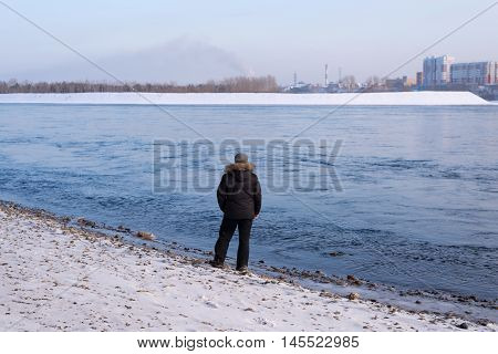 Man standing on a river bank on a cold winter day.