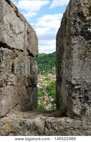 Beautiful hill town of Jajce viewed from a slit of the Jajce Fortress wall