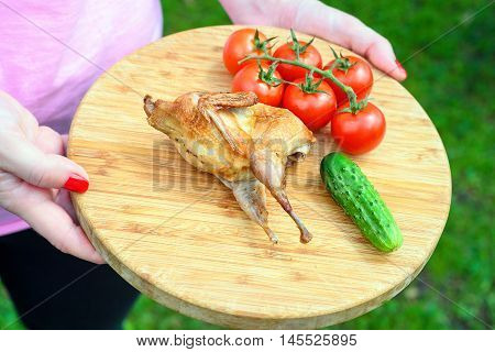 Delicious fried quail with fresh juicy vegetables on the wooden round board holding in hands. Prepared tomato, cucumber, partridge, quail.