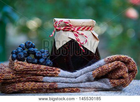 Grandma's gift. Homemade jam, knitted woolen socks and black chokeberry. Autumn concept.