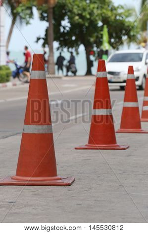 traffic warning cone in row to separate route in walkway for pedestrians.