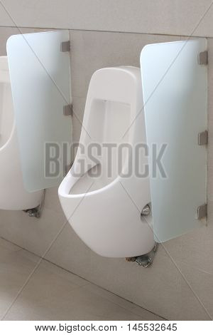 Modern urinal in men bathroom white ceramic urinals for men in toilet room.
