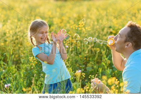 They always having fun together. Father and his daughter having fun outside and blowing bubble blower, smiling