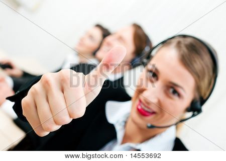 Group of three customer care representatives in a call center with headphones
