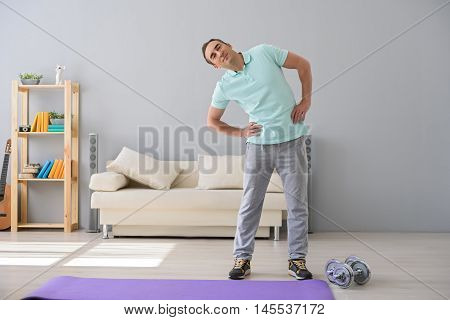 Healthy morning routine. Full height photo of muscular adult man doing workout, standing in room with dumbbells near him