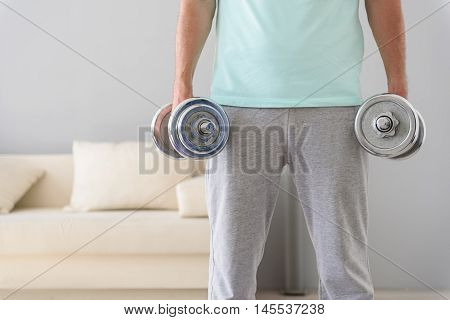 Try and keep up if you can. Close up of man using dumbbells to workout in bedroom with white sofa in background