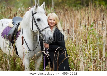 Blonde woman holds by bridle white horse among the reeds.