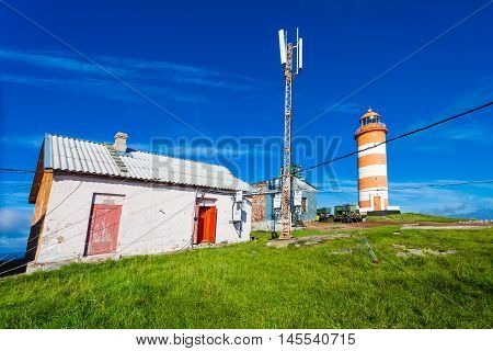 The telecommunication tower with of communications equipment (antennas) some buildings and the lighthouse on the top of island's hill