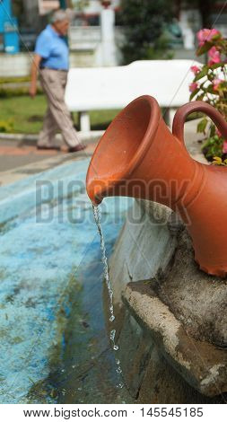 Banos de Agua Santa, Tungurahua / Ecuador - September 2 2016: Water flowing from crock in the fountain of Palomino Flores Park in the downtown of the city of Banos