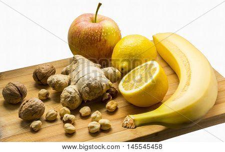 Fruits on the desk: apple, lemon, banana, nuts and ginger. Health food.